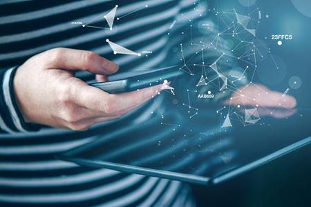 datos personales: Smartphone y la sincronización de datos de la tableta, mujer sincronizar archivos y documentos en los dispositivos electrónicos inalámbricos personales en el hogar, enfoque selectivo con poca profundidad de campo.