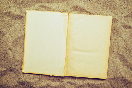 layoff: Open old vintage book with blank yellow pages as copy space flat laid in warm beach sand, top view.