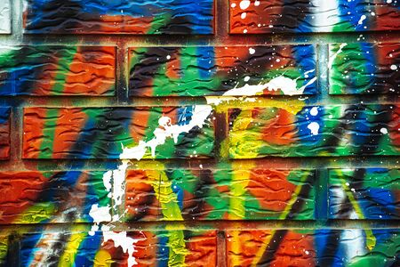 sprayed: Colorful paint sprayed brick wall, paint stains on urban surface.