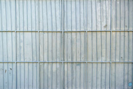 vertical bars: Aluminum metal platted garage wall, metallic surface texture with horizontal and vertical reinforcing bars as background.