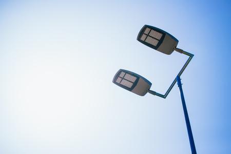 alumbrado: cancha de baloncesto al aire libre llevó aparatos de iluminación contra el cielo azul claro.