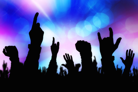 gig: Silhouettes of concert crowd hands supporting band performing live music on stage, young people on rock gig enjoying. Stock Photo