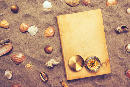 beach view: Vintage book and compass on sandy beach, vacation mood and summer lifestyle objects in flat lay top view arrangement. Stock Photo