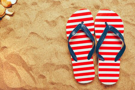 Pair of thongs or flip flops on beach sand, top view of summer holiday vacation accessories on sandy summertime resort coastline.