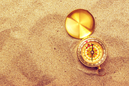 roam: Top view of vintage compass in beach sand, navigational equipment in warm brown sand of summer holiday vacation resort pointing to south.