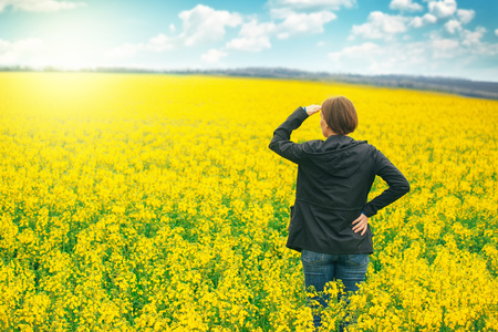 horizon: Woman agronomist standing in the field of blooming cultivated rapeseed plantation, female agricultural expert contolling the growth of agricultural crops and looking to distant point on the horizon. Stock Photo