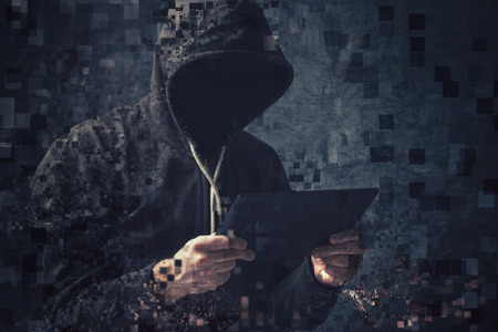 piracy: Pixelated unrecognizable faceless hooded cyber criminal man using digital tablet to access internet deep web page, p2p and piracy concept.