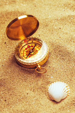 roam: Top view of vintage compass and sea shell in beach sand, navigational equipment in warm brown sand of summer holiday vacation resort pointing to south.