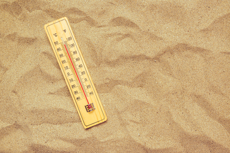 high scale: Record high temperatures, thermometer with celsius and farenheit scale on warm desert sand.