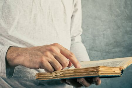 library book: Man reading old book with torn pages, close up of adult male hands holding vintage book. Stock Photo