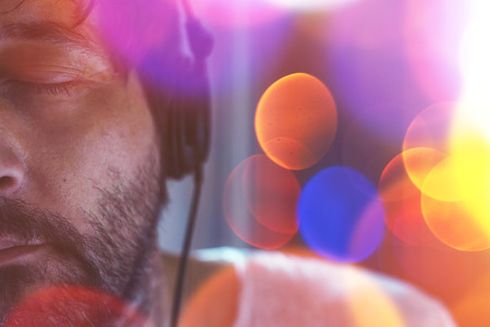 unshaven: Half face low key portrait of adult unshaven man listening to music on headphones with his eyes closed, enjoying favorite song, nice bokeh light