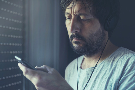 unshaven: Unshaven adult man listening to music on mobile phone with headphones