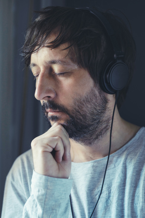 unshaven: Unshaven adult man listening to music on headphones by the window, enjoy favorite song with his eyes closed. Stock Photo