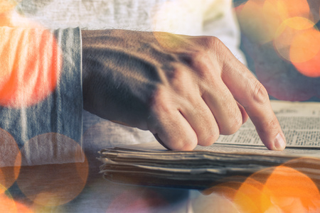 lexicon: Close up of adult male hands holding vintage book, man reading, bokeh light effect Stock Photo