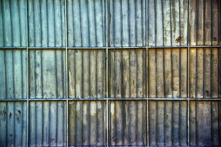 oxidized: Rusty oxidized aluminum metal platted garage wall, metallic surface texture with horizontal and vertical reinforcing bars as background.