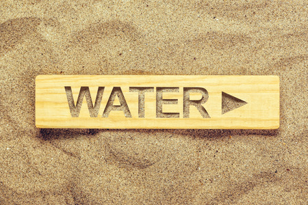 thirstiness: Water direction sign in dry desert sand, guide signpost for thirsty man.