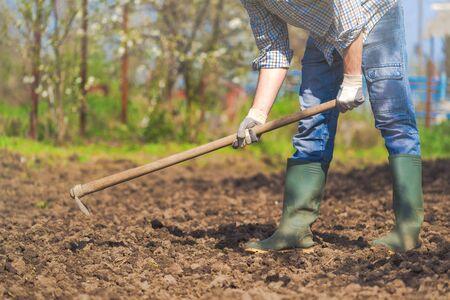 soil: Man hoeing vegetable garden soil, new growth season on organic farm. Stock Photo