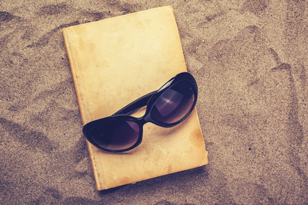 layoff: Reading favourite old book on summer vacation beach holiday, top view of a book and sunglasses in warm beach snow.