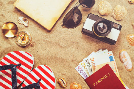 Summer vacation accessories on tropical sandy ocean beach, holidays abroad - summertime lifestyle objects and European euros in flat lay top view arrangement in warm sand.