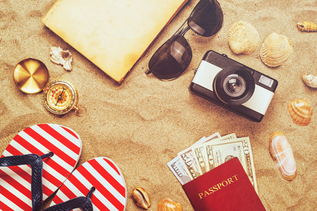 sand dollar: Summer vacation accessories on tropical sandy ocean beach, holidays abroad - summertime lifestyle objects and US American dollars in flat lay top view arrangement in warm sand.