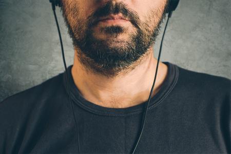 listening to music: hombre adulto sin afeitar escuchando música en los auriculares, disfrutar de una canción favorita, la mitad de la cara retrato oscuro