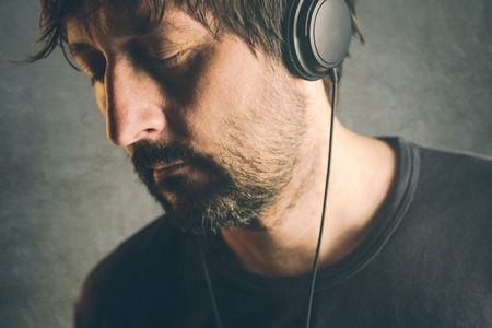 unshaven: Unshaven adult DJ man listening to music on headphones, enjoy favorite song with his eyes closed. Stock Photo