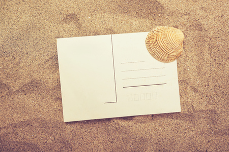 beach view: Blank postcard and sea shell in hot beach sand, top view of copy space for summer holiday vacation message in a letter, retro tone
