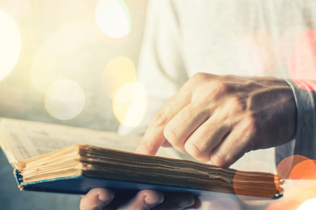 lexicon: Man reading old book with torn pages, close up of adult male hands holding vintage book, bokeh light in background.