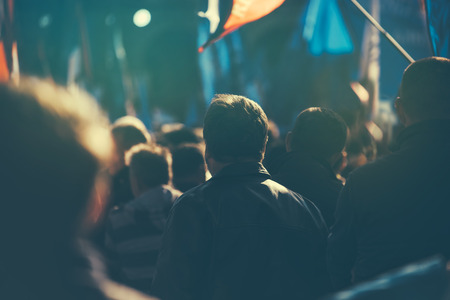 electioneering: Unrecognizable people on the street during political meeting, audience from behind, selective focus and retro toned image with lens flare. Stock Photo