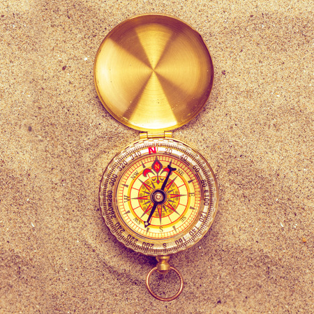 roam: Vintage compass in beach sand, navigational equipment in warm brown sand of summer holiday vacation resort pointing to south, square format, top view. Stock Photo