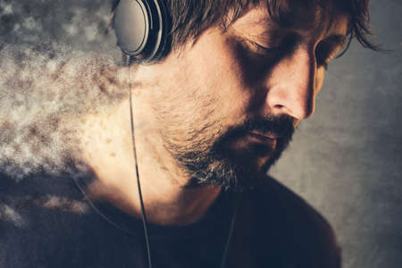 disintegrate: Unshaven adult male DJ listening to music on headphones, enjoy favorite song with his eyes closed and disintegrating into pieces.