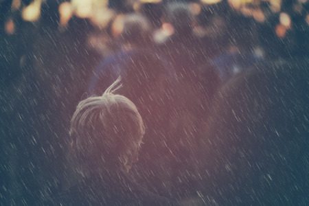 electioneering: Unrecognizable older adult person on outdoor political meeting from behind on rainy day, looking toward gathered crowd and stage.