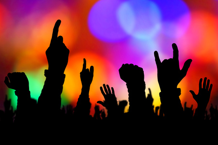 heavy metal: Silhouettes of concert crowd hands supporting band performing live music on stage, young people on rock gig enjoying. Stock Photo
