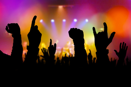 gig: Concert crowd hands supporting rock and roll band performing live music on stage, silhouettes of young people on rock gig enjoying. Stock Photo