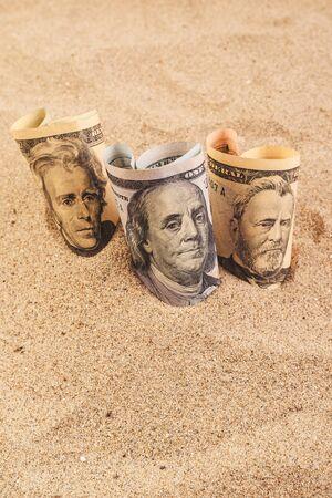 sand dollar: American dollar banknotes in hot desert sand