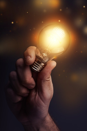 new ideas: Creative energy and power of new ideas, hand holding light bulb, retro toned image, selective focus. Stock Photo