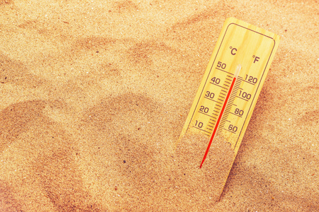 temperatures: Thermometer with celsius and farenheit scale on extremely warm beach sand showing record high temperatures
