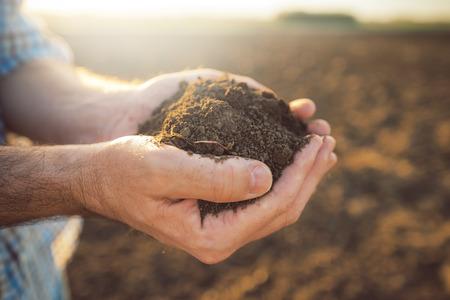 Handvol akkerbouw grond in handen van de verantwoordelijke landbouwer, close-up, selectieve aandacht Stockfoto