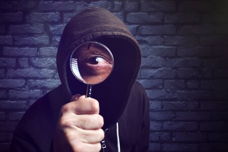 p2p: Hooded computer hacker with magnifying glass, internet hacker and online security concept.