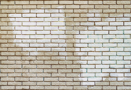 detrimental: Graffiti removal with white paint over covering on brick wall masonry surface, removing acts of vandalism. Stock Photo