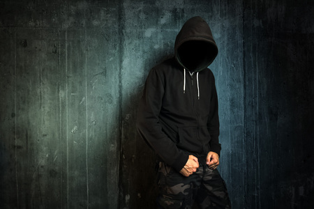 hooded shirt: Dangerous unrecognizable faceless criminal standing in front of concrete wall, crime rate and gangster lifestyle concept. Stock Photo