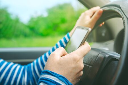 mobile sms: Female driving car and texting sms message on smartphone, using mobile phone in traffic, selective focus