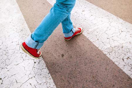 Jonge tiener persoon gekleed in een blauwe spijkerbroek en rood sneakers, wandelen over voetganger zebra zebrapad, selectieve aandacht Stockfoto
