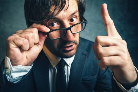 uptight: Angry tax inspector looking serious and determined, aggressive finger threatening adult businessperson with glasses