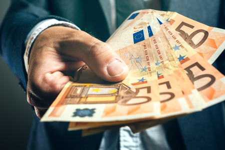 currencies: Businessman from bank offering money loan in euro banknotes, selective focus.