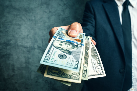 Businessman from bank offering money loan in USA dollar banknotes, selective focus.