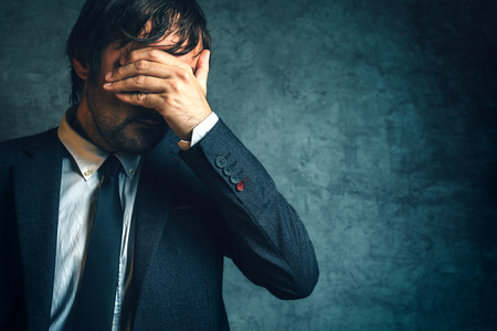 under pressure: Unhappy businessman under stress after business project failure, hand covering eyes. Stock Photo