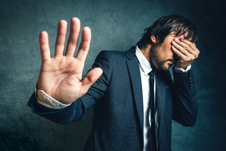covering eyes: Stressed businessman after business project failure, covering eyes in despair and hand gesturing stop to camera.