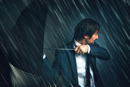 difficulties: Business challenge and difficulties concept with businessman standing in rain storm with open umbrella