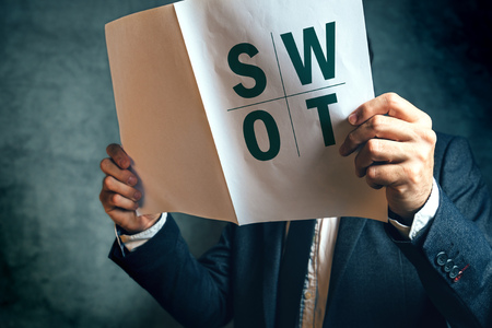 strong strategy: Businessman reading SWOT analysis report documentation, male businessperson in office